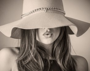A woman with a floppy hat hanging over her eyes