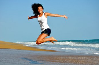 A woman jumping in the air on a beach