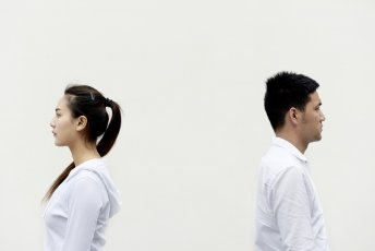 A man and woman in white with their backs to each other