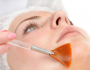 A woman having a skin peel applied to her face